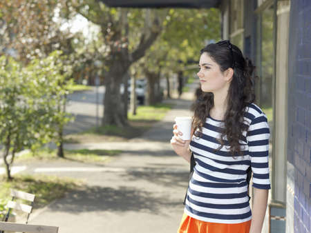 Young woman with takeaway coffee waiting on street