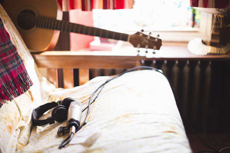 rehearse: Headphones and microphone on sofa, guitar in background