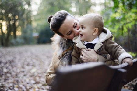 Mother holding male toddler on woodland park bench LANG_EVOIMAGES