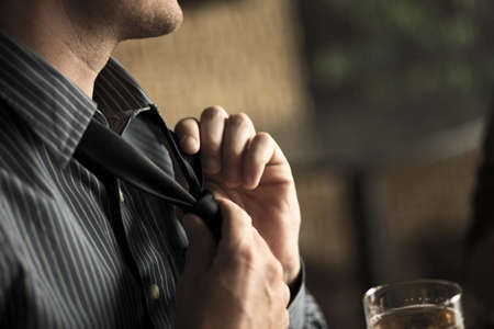 beer necktie: Close up of businessman loosening tie in a wine bar