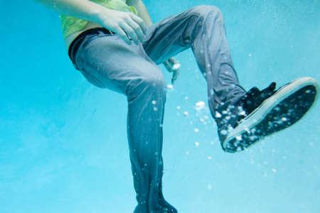 pantalones abajo: Cerca de las piernas masculinas vestidas completamente bajo el agua