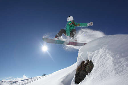 Young woman jumping with snowboard, Mayrhofen, Tyrol, Austria