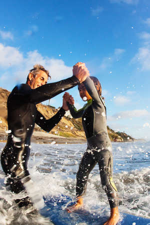 Father and daughter jumping in sea,Encinitas,California,USA