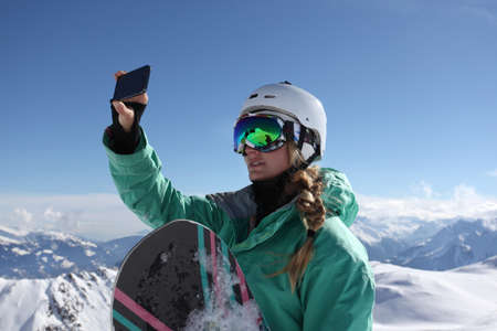 Young female snow boarder photographing view, Mayrhofen, Tyrol, Austria