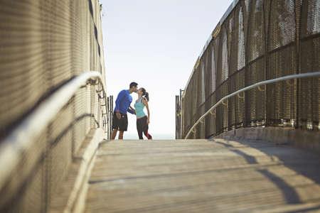 Joggers on bridge kissing