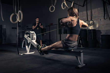 dimly: Woman using rowing machine in gym
