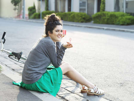 Portrait of young woman eating ice cream on sidewalk