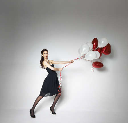 saint: Woman pulling back escaping heart-shaped balloons