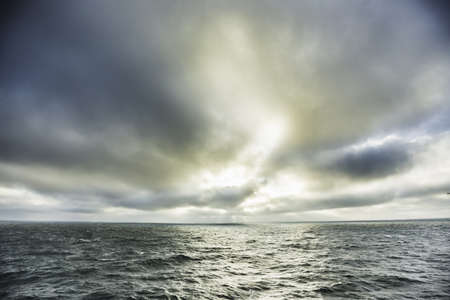 Sea and stormy sky with sunlight reflected on water