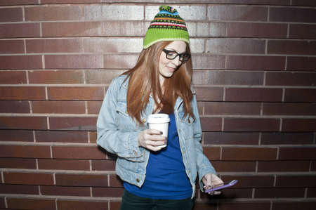 Young woman with takeaway coffee looking at smartphone LANG_EVOIMAGES