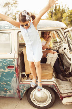 Girl jumping from campervan with arms out