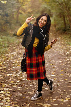 Young woman in park,listening to music using earphones,making peace sign LANG_EVOIMAGES