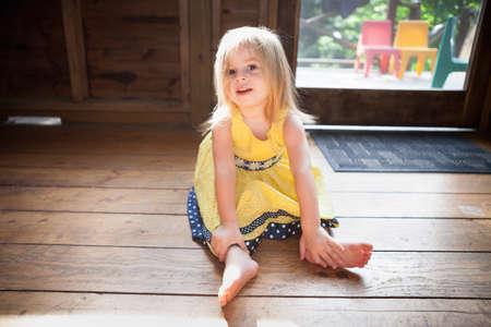 Female toddler sitting on wooden floor