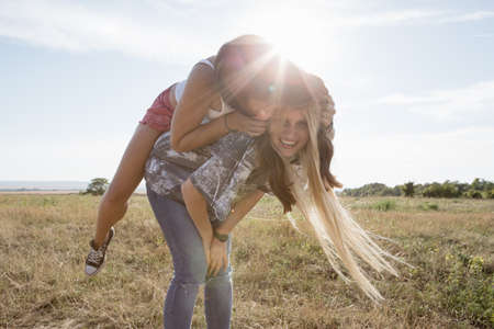 Young woman giving friend piggy back