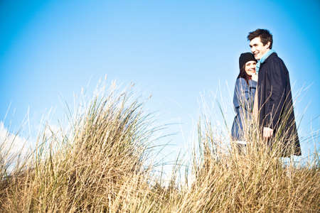 Couple standing in sand dunes, Bournemouth, Dorset, UK