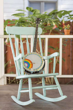 Banjo and rocking chair on outside porch LANG_EVOIMAGES