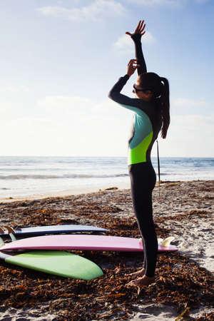 Mid adult woman preparing to surf,Encinitas,California,USA