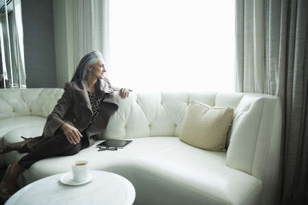 handheld device: Portrait of mature woman reclining on white luxury sofa