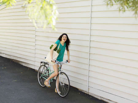 passageways: Young woman cycling along alley with shopping