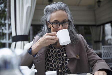 Reife Frau trinkt Kaffee auf Luxus Veranda LANG_EVOIMAGES