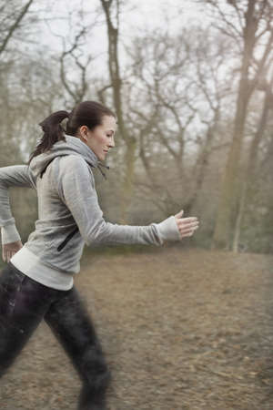 detoxing: Young woman running through forest