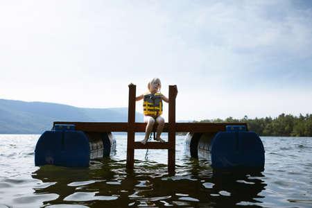 Female toddler sitting on floating platform,Silver Bay,New York,USA LANG_EVOIMAGES