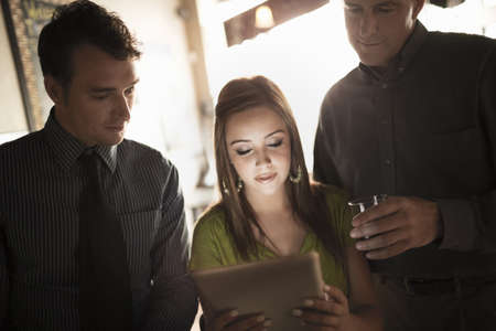 electronic commerce: Business colleagues looking at digital tablet in a wine bar