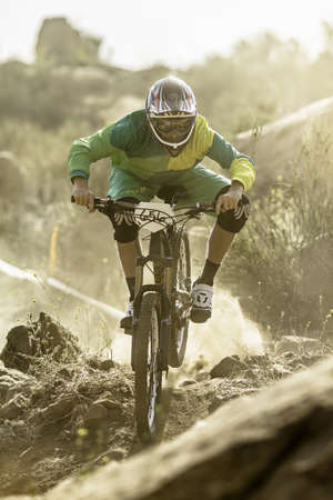Male mountain biker racing on dusty track, Fontana, California, USA