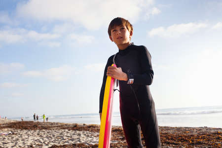 Young boy with surfboard on beach,Encinitas,California,USA LANG_EVOIMAGES