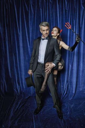 Male entertainer with burlesque dancer holding devils fork