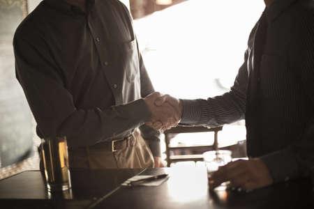 Two businessmen shaking hands in wine bar LANG_EVOIMAGES