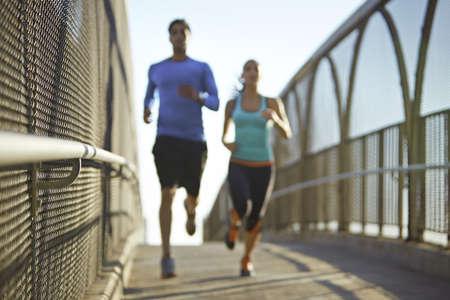 Man and woman running over bridge