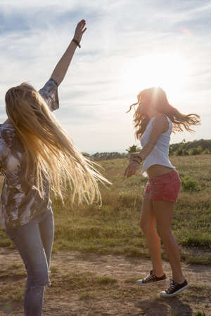 Two young women dancing in field LANG_EVOIMAGES