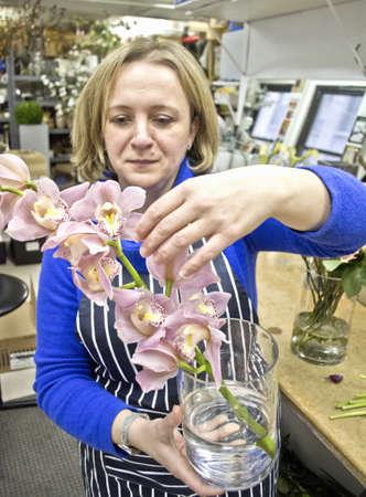 Floral designer arranging orchids in studio