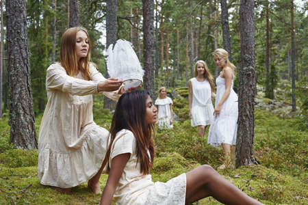 Teenage girl putting white hat on friend in forest