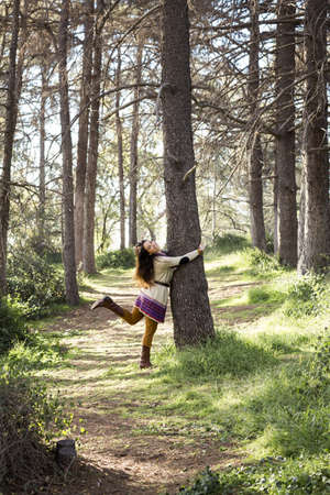 Young woman hugging tree trunk in forest LANG_EVOIMAGES