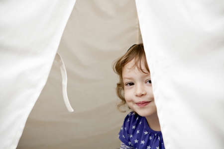Portrait of female toddler peeking out of tent