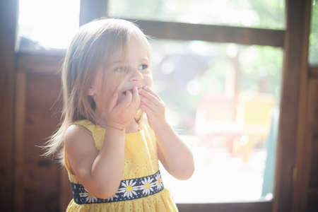 Close up of female toddler with hands over mouth