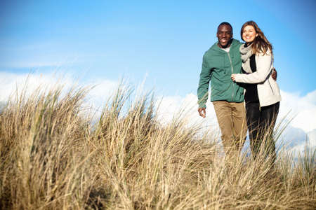 Young couple strolling in sand dunes, Bournemouth, Dorset, UK