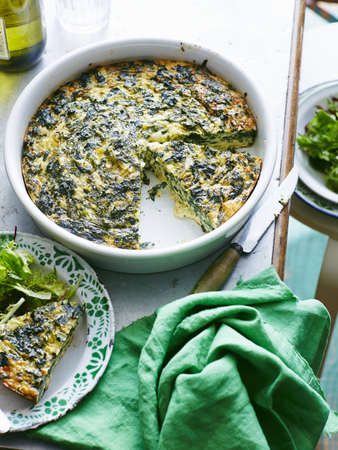 Dish of silverbeet and feta frittata with portion on plate