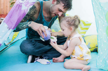 Young man and toddler daughter playing with teacup in tent LANG_EVOIMAGES