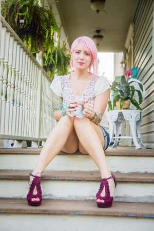 Portrait of young woman with pink hair sitting on porch steps LANG_EVOIMAGES
