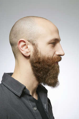 Studio profile portrait of mid adult man with shaved hair and overgrown beard
