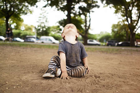 casual clothing 12 year old: Male toddler sitting in park looking up