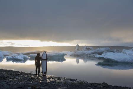 Woman with surfboard, Jokulsarlon Glacier Lagoon, Skaftafell National Park, Iceland LANG_EVOIMAGES