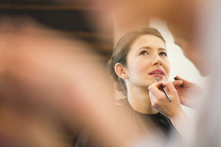 ceremonial make up: Female friend applying lip liner to brides lips