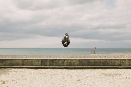 athletic wear: Parkour athlete experimenting with movement on beach, Sussex, United Kingdom