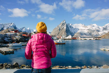 Woman by cod fishing village, Lofoten, Norway LANG_EVOIMAGES