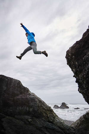 Man leaping over rocks, Prairie Creek Redwoods State Park, California, US