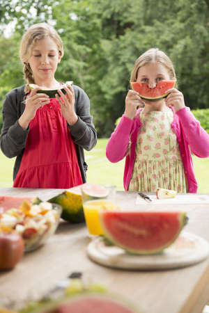 Two sisters at patio table eating and holding up watermelon slice LANG_EVOIMAGES